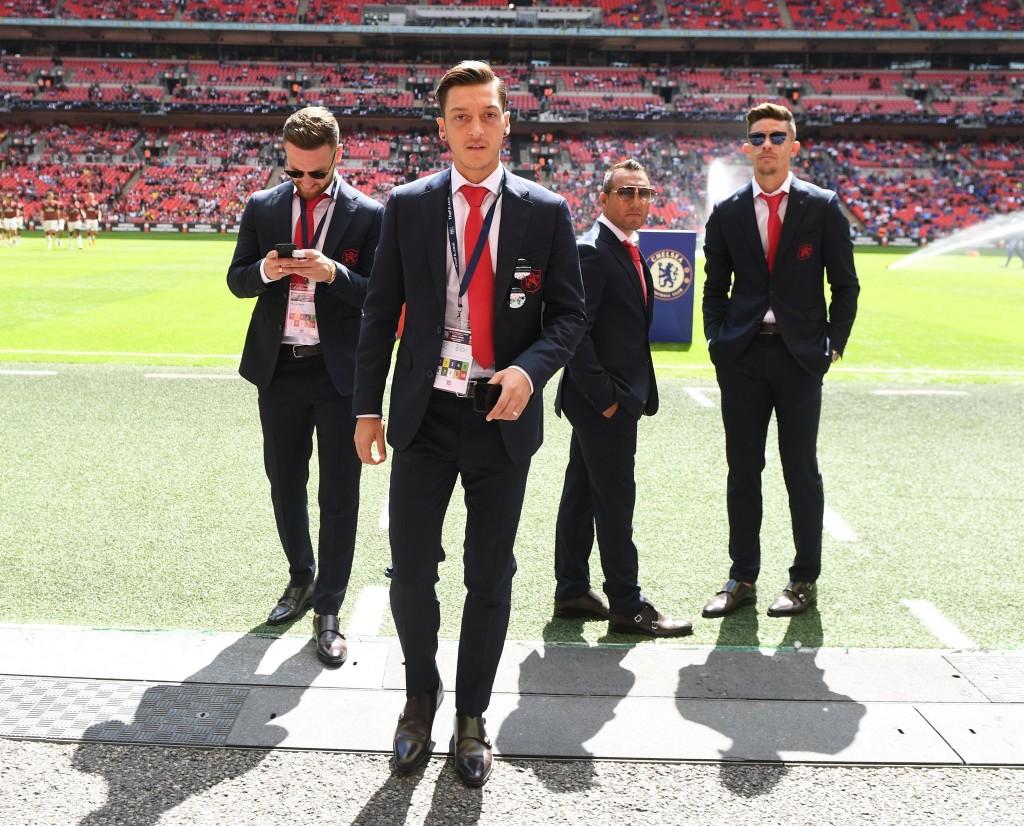 Mesut Ozil je včeraj s tribune pospremil zmago svojih soigralcev nad Chelseajem. Vidno zadovoljen jim je po tekmi prišel čestitati na igrišče, zraven pa je bilo moč opaziti tudi Alexisa Sancheza. Tako je dvojica vsaj za nekaj časa utišala govorice o prestopu. Vir slike: Arsenal